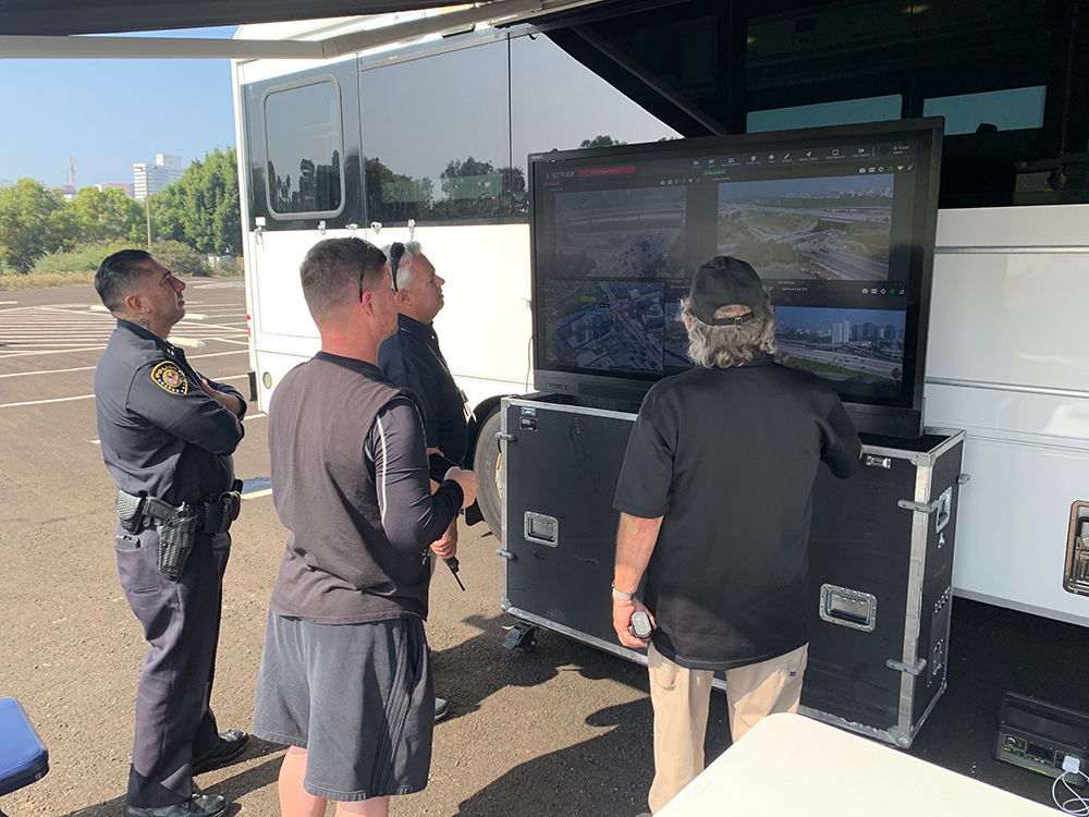 Senior figures from the US Department of Veteran Affairs gather round the MIU-55, which provided situational awareness, outside a command bus  during a political rally